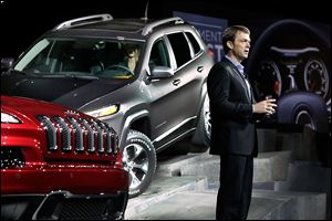 Mike Manley, chief executive for the Jeep brand, presents the 2014 Jeep Cherokee Limited, left, and Cherokee Trailhawk at the New York International Auto Show at the Javits Center.