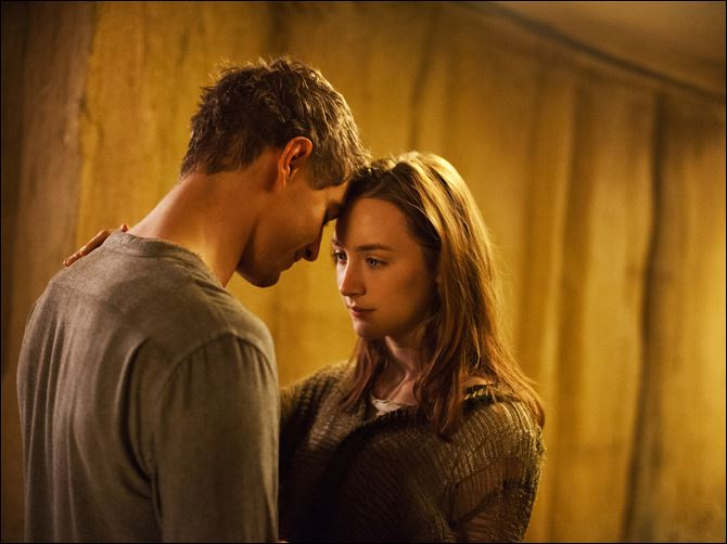 "Max Irons, left, and Saoirse Ronan in a scene from ""The Host."""