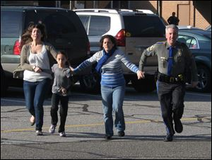In this Dec. 14, 2012 file photo provided by the Newtown Bee, a police officer leads two women and a child from Sandy Hook Elementary School in Newtown, Conn., shortly after Adam Lanza opened fire, killing 26 people, including 20 children.