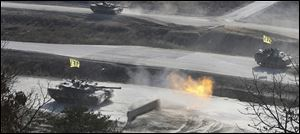 A South Korean K1 army tank fires live rounds during an exercise at Seungjin Fire Training Field in mountainous Pocheon, South Korea, near the border with North Korea, Wednesday, March 27, 2013.