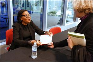 Author and guest speaker Jamaica Kincaid chats with Susan Haley of South Toledo, right, while signing books at the Main Library in downtown Toledo.