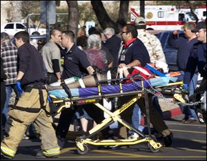 FILE - In this Jan. 8, 2011 file photo, Emergency personnel and Daniel Hernandez, an intern for U.S. Rep. Gabrielle Giffords, second right, move Giffords after she was shot in the head.