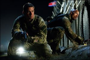 Channing Tatum, left, as Duke and Dwayne Johnson as Roadblock in a scene from the film,
