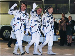 Russian Cosmonauts Alexander Misurkin, right, Pavel Vinogradov, center, and U.S. astronaut Christopher Cassidy, crew members of the mission to the International Space Station, ISS, walk prior launch.
