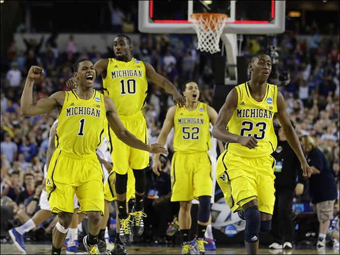 Michigan's Glenn Robinson III (1), Tim Hardaway, Jr. (10), Jordan Morgan (52), and Caris LeVert (23) celebrate after the Wolverines advanced to the Elite Eight.