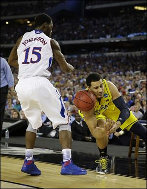Kansas' Elijah Johnson strips the ball from Michigan's Jordan Morgan during the second half Friday in Arlington, Texas.