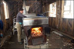 Johanna Lake checks the evaporator at David Moore's Crooked Chimney sugarhouse  Lee, N.H. Moore, New Hampshire''s only known commercial birch syrup producer, got his start in 2008, when he was a student at the University of New Hampshire.