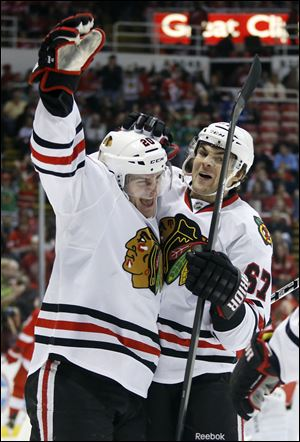 Chicago Blackhawks left wing Brandon Saad, left, celebrates his first period goal with Chicago Blackhawks right wing Michael Frolik (67), of the Czech Republic, during an NHL hockey game against the Detroit Red Wings Sunday, March 31, 2013, in Detroit. (AP Photo/Duane Burleson)
