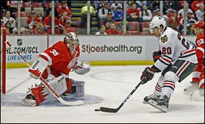 The Blackhawks' Brandon Saad drives onto Red Wings goalie Jimmy Howard for one of his two goals in Chicago's 7-1 rout.