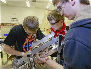 Mark Damazyn, left, Charlie Cook, center, and Matt Stewart of the Bedford Express team work on the shooter for the Frisbee-throwing part of the competition, one of two functions the robot is to perform.