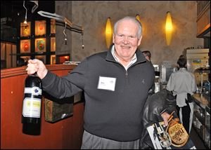 Don Harbaugh shows the bottle of wine he purchased at th