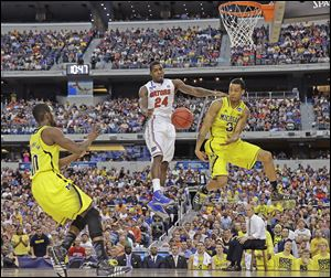 Michigan's Trey Burke (3) passes the ball to Tim Hardaway, Jr., in front of Florida's Casey Prather for an easy dunk in the second half. The Wolverines  (30-7) will play Syracuse (30-9) in the Final Four on Saturday night in Atlanta.