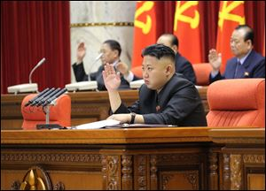 North Korean leader Kim Jong Un raises his hand with other officials to adopt a statement during a plenary meeting of the central committee of the ruling Workers' Party in Pyongyang, North Korea Sunday.