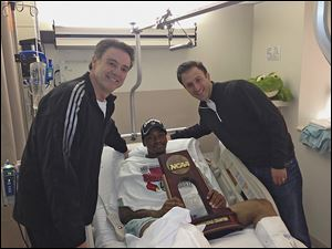 Injured Louisville guard Kevin Ware was brought the trophy from Sunday's win by coach Rick Pitino, left, and former team assistant coach Richard Pitino.
