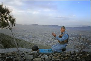 An Afghan police officer offers evening prayers with Kabul, Afghanistan, in the background. Afghan President Hamid Karzai held talks Sunday with the emir of Qatar during a visit to discuss a Taliban presence in Qatar.