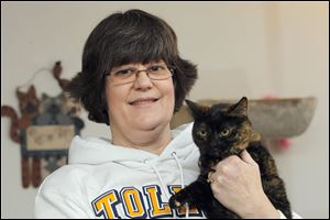 Jill Falls of Sylvania Township holds Monkey, who, along with Ms. Falls' other cats, has experienced dental problems.