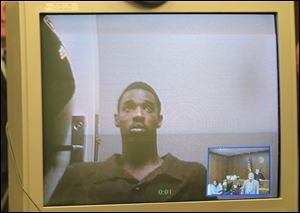 Jonathon Johnson, 23, is arraigned via a video appearance today in Toledo Municipal Court on a charge of aggravated murder.
