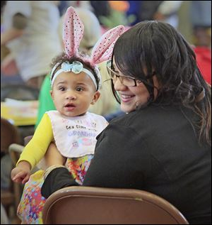 Kelsea Hueston of Toledo holds her daughter Maurissa Robin-son at the dinner, which featured traditional Easter fare.