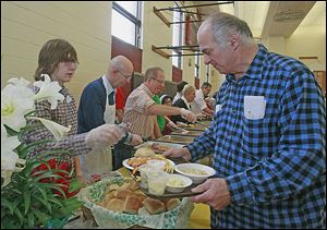 Chase Smith, 15, of Macomb, Mich., left, serves William Stowe of Toledo a roll as part of the dinner.   Christ the King Church hosts a free Easter Sunday dinner for all who want to attend.