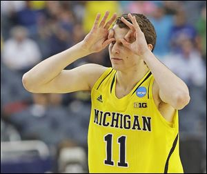 Michigan's Nik Stauskas reacts after making a 3-pointer shot during the first half of a regional final game against Florida. Stauskas hit all six of his 3-pointers and finished with 22 points.