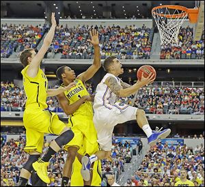 Florida's Scottie Wilbekin tries to get off a shot as Michigan's Glenn Robinson III (1) and Nik Stauskas defend during the first half in Arlington, Texas. Wilbekin finished with four points for the Gators.