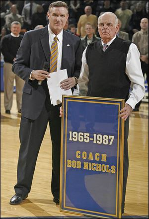 Mike O'Brien, University of Toledo athletics director, left, and Bob Nichols watch as a banner is raised in honor of the former coach at Savage hall in 2008.