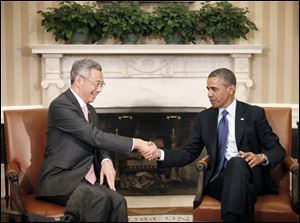 President Barack Obama shakes hands with with Singapore Prime Minister Lee Hsien Loong during their meeting in the Oval Office of the White House in Washington.