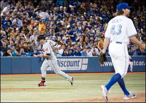 Cleveland shortstop Asdrubal Cabrera rounds the bases past Toronto Blue Jays R.A. Dickey after hitting a two-run home run during the fifth inning Tuesday in Toronto.