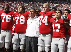 Ohio State offensive lineman Jack Mewhort, 74, joins coach Urban Meyer, and teammates, in the singing of 'Carmen Ohio,' following their game against Central Florida last season at Ohio Stadium in Columbus.