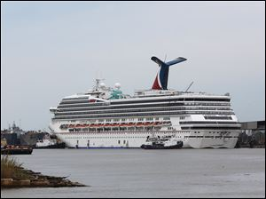 Tug boats maneuver around the Carnival cruise ship Triumph as it rests against a dock on the east side of the Mobile River after becoming dislodged from its mooring at BAE Shipyard during high winds Wednesday, April 3, 2013 in Mobile, Ala.