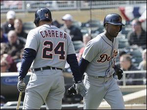 Detroit Tigers' Miguel Cabrera, left, congratulates Austin Jackson after Jackson scored on a ground out by Torii Hunter off Minnesota Twins pitcher Mike Pelfrey during the first inning.
