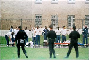 Inmates raise their hands in surrender during a riot at the Southern Ohio Correctional Facility in Lucasville. The 1993 siege lasted 11 days.