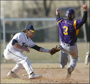St. John's Jim Scott tags out Maumee's Tommy Henry at second base during the fifth inning. Maumee grabbed a 3-0 lead before the Titans stormed back for an 8-7 non-league victory.