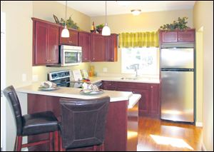 Cherry cabinets with crown molding and stainless steel appliances are very stylish.