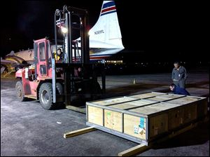 A box containing  a giant saltwater crocodile sits on the tarmac at Toledo Express Airport after it was taken off a cargo plane after arriving Friday night.