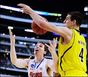 Michigan's Mitch McGary knocks the ball away from Florida's Erik Murphy. McGary has averaged 17.5 points and 11.5 rebounds per game for the Wolverines in the NCAA tournament.