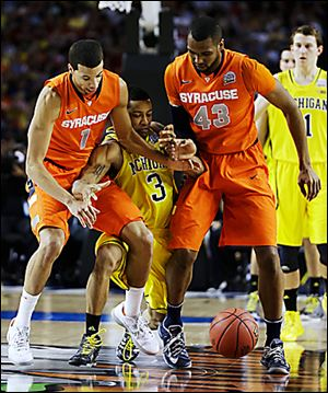 Syracuse's Michael Carter-Williams (1) and James Southerland (43) vie for a loose ball Michigan's Trey Burke during the first half.