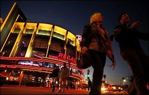 People walk in front of the Regal Cinemas LA Live Stadium 14 in Los Angeles, California, on February 14, 2013. Movie theater chains are putting pressure on studios to pay more to have their trailers placed in front of the audiences they want.