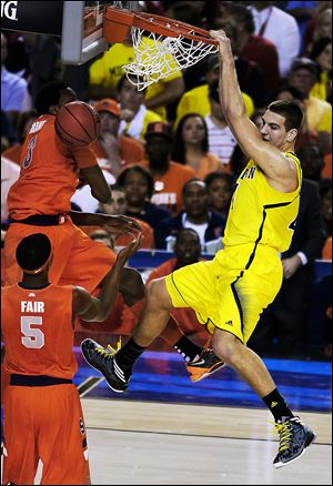 Michigan's Mitch McGary dunks the ball against Syracuse's Jerami Grant (3) and C.J. Fair during the first half. McGary also had a pair of blocks early in the Final Four contest in the Georgia Dome in Atlanta on Saturday evening.
