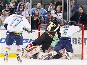 Walleye goalie Kent Simpson is knocked into his goal by Cincinnati's Taylor Ellington (6) and teammate Wes O'Neill.