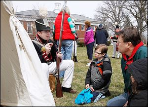 Pvt. Steve Nichols shows Toledoan Stephen Eckloff, 8, and his father, Brian Eckloff, how a musket works during a Remembering the War of 1812 program at the Maumee branch library Saturday.