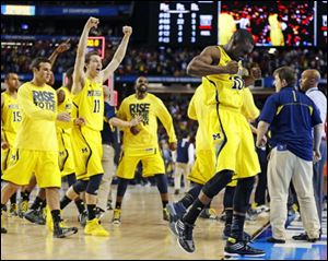 Michigan players including Tim Hardaway Jr., right, and Nik Stauskas (11) celebrate after defeating Syracuse on Saturday in Atlanta.