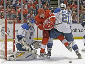 The Blues' Patrik Berglund (21) defends against the Red Wings' Justin Abdelkader (8) in front of goalie Brian Elliott (1) in the second period on Sunday. Berglund had an assist in the lone goal in the game while Elliott made 28 saves for the shutout.