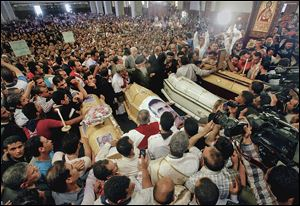 Coptic Christians gather around four coffins during a funeral service Sunday at St. Mark's Coptic Orthodox Cathedral in Cairo. Violence after the funeral for the four Christians who were killed Friday led to another person dead and 84 injured.