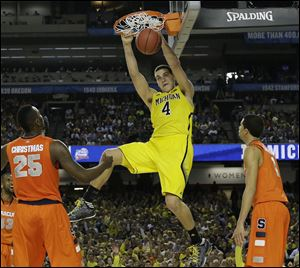 Michigan's Mitch McGary dunks the ball against Syracuse during the second half of the national semifinal on Saturday. McGary has been the Wolverines' leading scorer and rebounder during their postseason run.