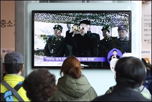 People watch a TV program showing North Korean leader Kim Jong Un at Seoul Railway Station in Seoul, South Korea, today.