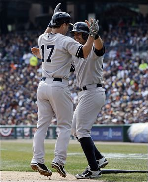 New York Yankees' Jayson Nix (17) is congratulated by teammate Francisco Cervelli after they both scored on Nix's two-run home run during the second inning of a baseball game against the Tigers in Detroit.