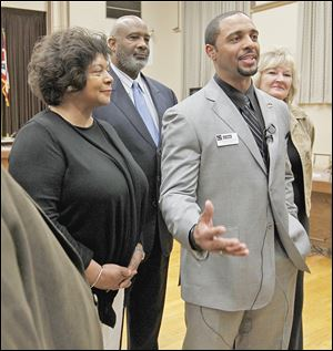 From left, Dr. Cecelia Adams, Larry Sykes, and Lisa Sobecki stand behind Romules Durant after the Board of Education selected Mr. Durant as the interim superintendent of Toledo Public Schools during a meeting Monday at the board's office.