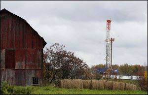 A drilling rig is set up near a barn in Springville, Pa., to tap gas from the giant Marcellus Shale gas field. A new plan to strengthen standards for fracking is creating unusual divisions among environmentalists and supporters for the oil and gas industry. Some environmentalists say the new partnership between the gas companies and environmentalists is too soft. Others in the industry complain the program, announced March 20, goes too far.