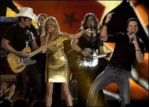 From left, musicians Brad Paisley, Cheryl Crow, and Luke Bryan perform on stage Sunday at the 48th Annual Academy of Country Music Awards at the MGM Grand Garden Arena in Las Vegas. Bryan immediately overshadowed top winner Miranda Lambert's big night by beating out some of country music's top performers to win entertainer of the year.
